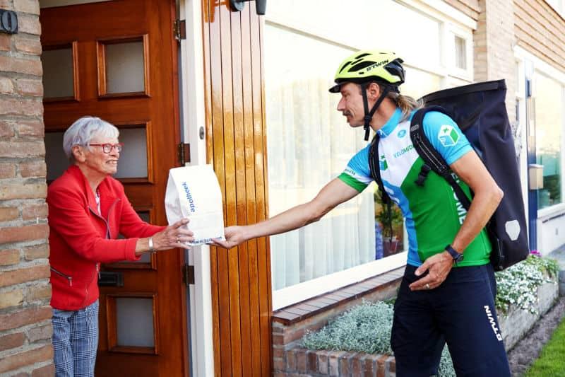 Een fietskoerier overhandigd medicijnen aan apotheek klant